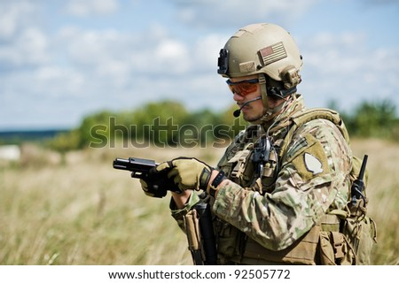 The soldier  in full gear reloads a gun - stock photo