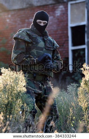 The soldier with gun is outdoor in nature.