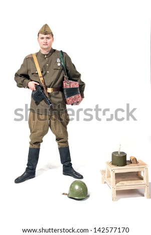 The soldier with the accordion near military tackles - stock photo