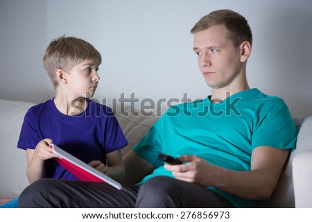 The son asks his father to help him with homework