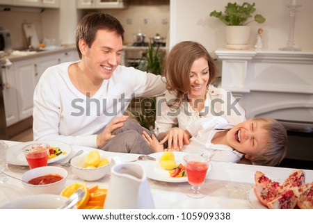 The son of entertains its parents after dinner in the modern kitchen - stock photo