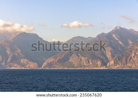 The south coast of Crete. View of the Samaria Gorge in Agia Roumeli from the mediterranean sea at evening. The Lefka Ori or White Mountains is one of the most beautiful landscapes on Crete. - stock photo