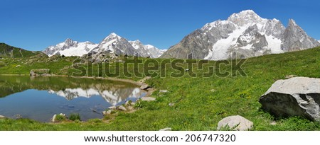 The south face of Mont Blanc (italian side), from the Vesses lake in Val Veny valley along the famous Tour du Mont Blanc trail. Courmayer, Valle d'Aosta, Italy. - stock photo