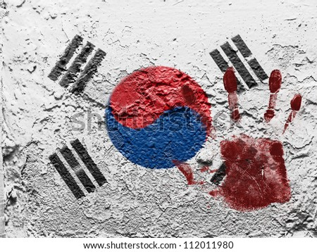 The South Korea flag painted on grunge wall with bloody palmprint over it