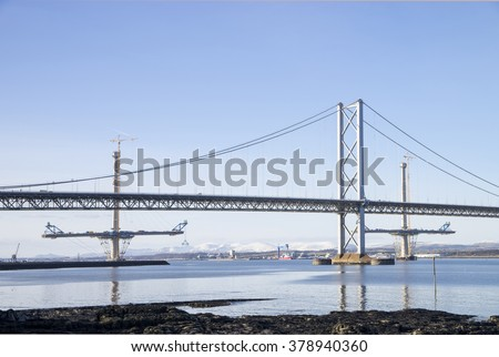 The South Queensferry end of the Forth Road Bridge, with two partially-completed towers and deck of the new Queensferry Crossing in the background - stock photo