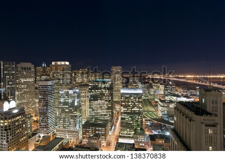 The southern end of downtown San Francisco, the bay, and the Bay Bridge at night from above - stock photo