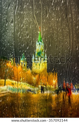 The Spasskaya Tower is the main tower with a through-passage on the eastern wall of the Moscow Kremlin, which overlooks the Red Square. Night view throw a wet glass in a rainy evening. - stock photo