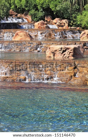 The spectacular cascade fountain. Multistage stone fountain surrounded by tropical vegetation and palm trees - stock photo