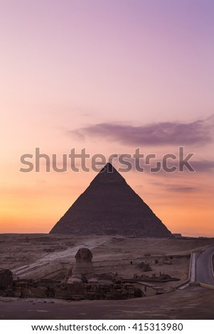 The Sphinx at sunset with great pyramid of Giza in background. - stock photo
