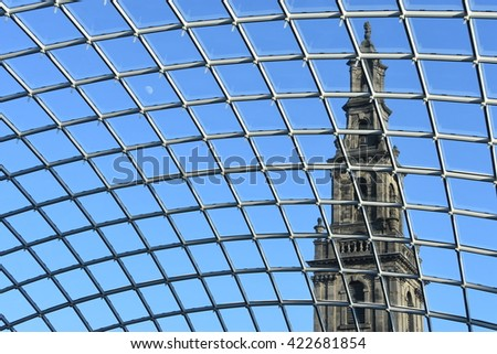 The spire of Holy Trinity Church through the glass roof of Leeds Trinity Shopping Mall - stock photo