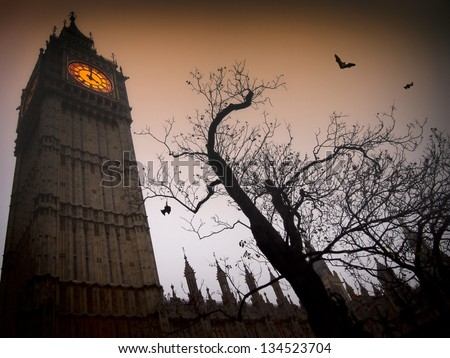 The spooky clock tower of Westminster with a bare tree and flying bats - stock photo