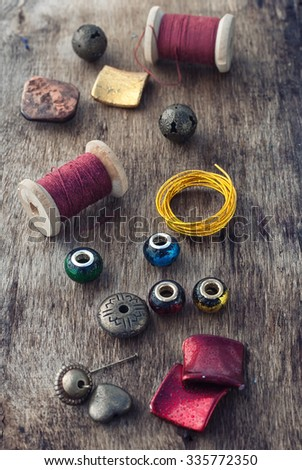 The spool of thread,beads and wire for needlework on wooden background. - stock photo