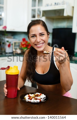 The sports young woman with a protein cocktail in a shaker and plate with nutritional supplements  sits in house kitchen. Sports nutrition. - stock photo