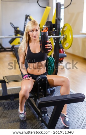 The sports young woman with a protein cocktail in a shaker sits in a gym. Sports nutrition. - stock photo