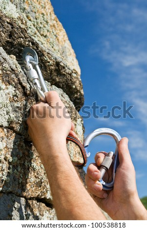 The sportsman hangs up carbine and guy-rope in rock - stock photo