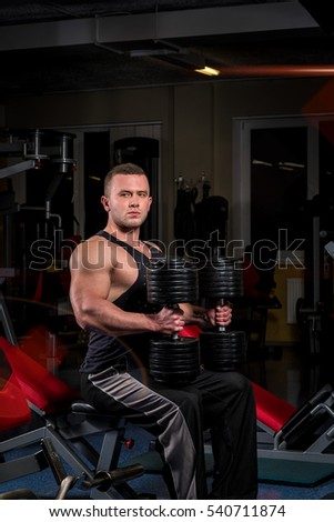 The sportsman on a bench with dumbbells.