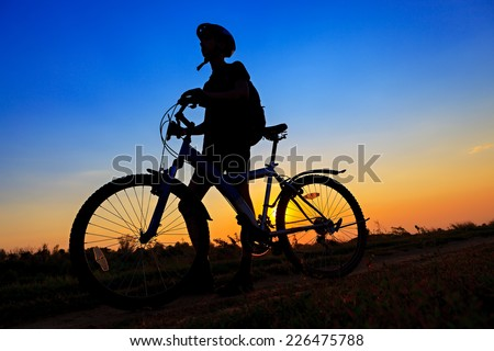 The sportsman on a bicycle traveling on the road on sunset background. - stock photo
