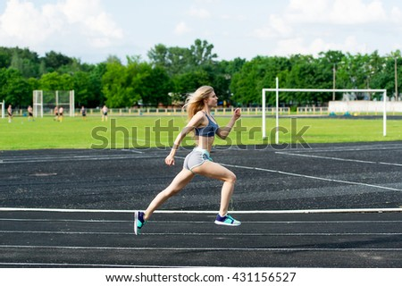 The sportswoman runs on a path at stadium. The girl is engaged in sprint.