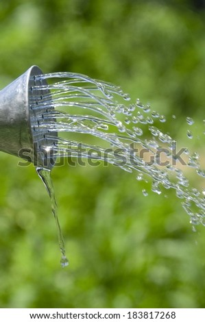 The spout of a watering can pouring water. - stock photo