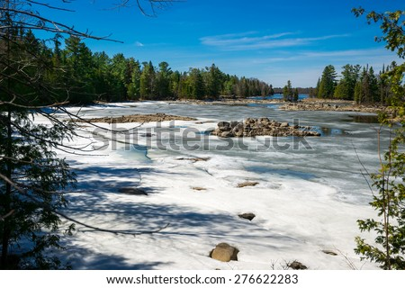 The spring thaw melts the snow covering a lake inlet in the wilderness of Ontario, Canada.