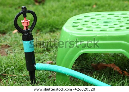 The sprinkler unit put on the garden lawn represent the gardening equipment concept related idea. - stock photo