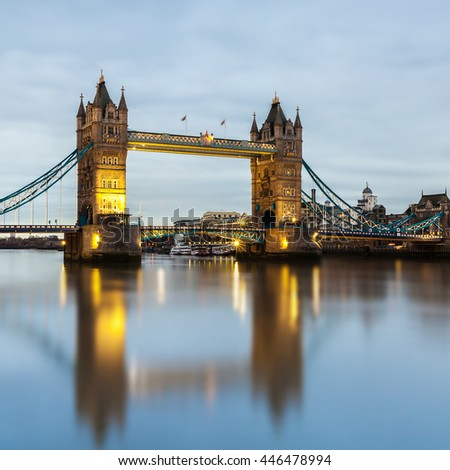 The square image of Tower Bridge, London, with motion blur reflection in the River Thames, taken in the early cloudy morning.