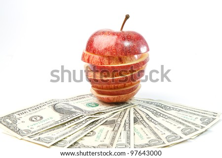 The stack of dollars lays on an apple - stock photo