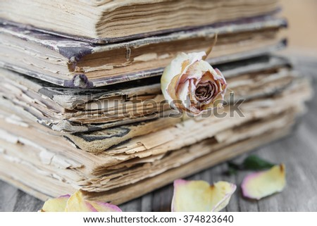 The stack of old books and Dried rose lying on an old wooden board
