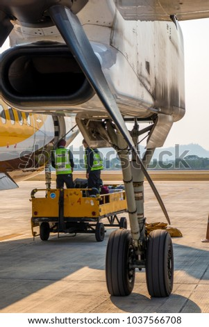 The staff are bringing luggage to the Nok Air airplane before leaving in the afternoon at Chiang Mai airport , Chiang Mai province , Thailand. 26 Feb 2018