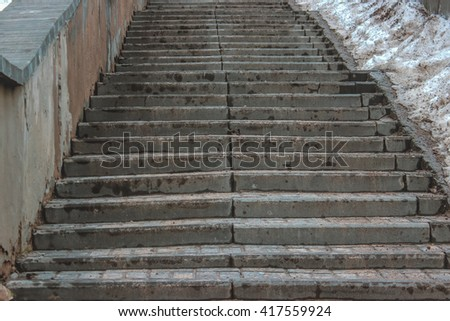 The staircase leading up, in which the people rise or fall. Stairs from the sidewalk stone. Stairs next to dirty snow. - stock photo