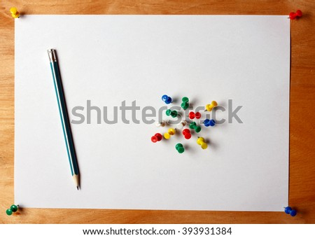 The standard A4 sheet of paper attached pushpin to a wooden board. On paper is a pencil and colored buttons - stock photo
