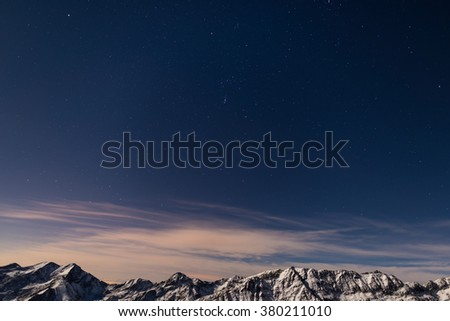 The starry sky captured on the Alps in winter. The Pleiades, Orion Constellation, Betelgeuse and Sirio star clearly visible. Snowcapped mountain ridge glowing under moonlight. Low digital noise. - stock photo