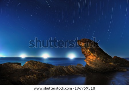 The stars rotate in the sky behind the foreground of rocky cliffs. - stock photo