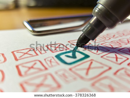 The stated tick green marker among many red squares and crosses on a white paper on the tablet - stock photo