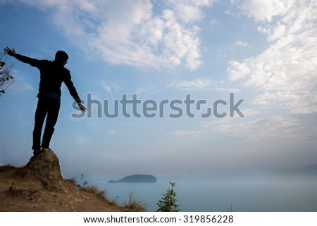 The Statue man standing on stones at top hills with in haze view of the sea, island and skies.