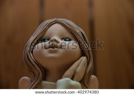 The statue of an angel girl with wings and folded hands on the wooden background - stock photo