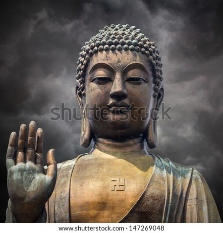 The statue of Big Buddha face with hand in Hongkong on  storm clouds background  - stock photo