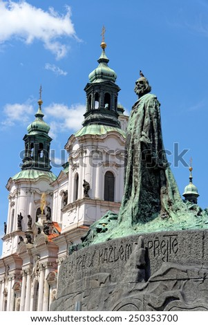 The statue of Jan Hus, one of the most important personalities in Czech history, in Old Town Square in Prague and St Nicholas church in the background. He was burnt as a heretic for reformist ideas. - stock photo