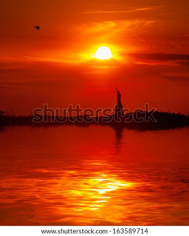 The Statue of Liberty and the setting sun with water reflection - stock photo