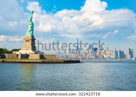 The Statue of Liberty with the downtown Manhattan skyline on a beautiful summer day - stock photo
