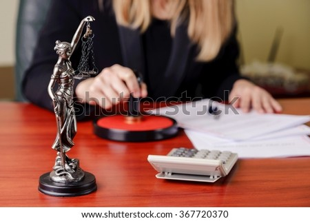 The statue of Themis on the background of a working woman - notary public - stock photo