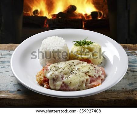 The steak parmigiana with potato and rice - stock photo