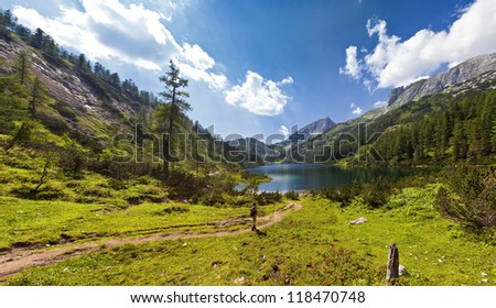 The Steirersee (1.447m) is a mountain lake of Tauplitzalm/Austria and surrounded by natural forest. The mountain range on the right is part of the Toten Gebirge.