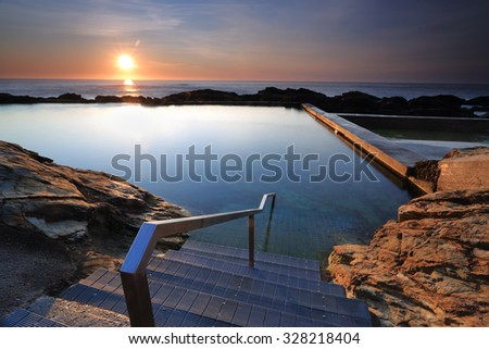 The steps leading down into the Blue Pool, Bermagui, just after the sunrise, a nice place for a swim or to relax. - stock photo