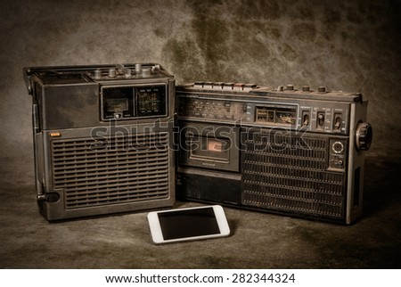 the still life retro ghetto blaster and new smartphone on grunge background - stock photo