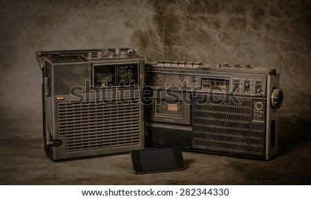 the still life retro ghetto blaster and new smartphone on grunge background