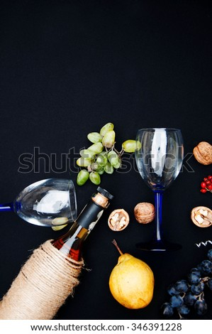 The still life with white wine in glass bottle on black background. Glasses of wine with fresh grapes. Bottle and footed glass. Fresh ripe white grapes, walnuts, juicy ripe pear. Drink. Rustic style. - stock photo