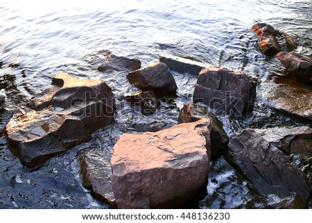 the stones in the water on the shore - stock photo
