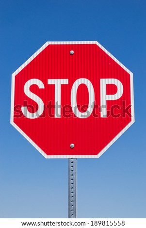 The stop sign in the Californian blue skies.