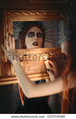 The strange goth girl holding candle in hand and looking into the mirror - stock photo